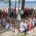 kāzu kopbilde sirds formā, viesi pie jūras