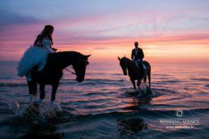 kāzu izjāde ar zirgiem pie jūras, saulriets kāzās